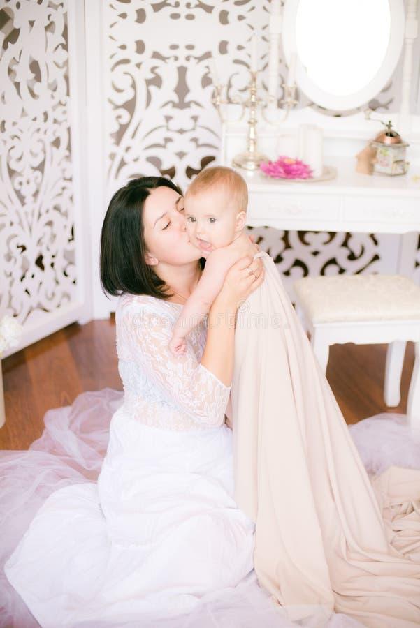 Jong mamma met een baby in haar wapens in de heldere slaapkamer royalty-vrije stock fotografie
