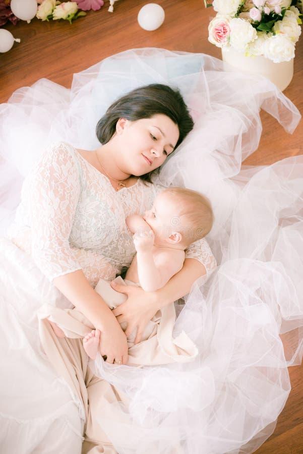 Jong mamma met een baby in haar wapens in de heldere slaapkamer stock fotografie