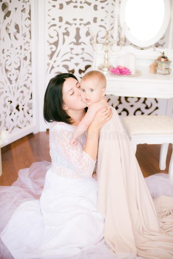Jong mamma met een baby in haar wapens in de heldere slaapkamer stock afbeeldingen