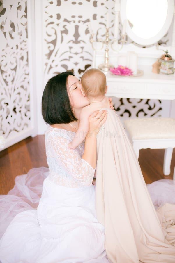 Jong mamma met een baby in haar wapens in de heldere slaapkamer royalty-vrije stock foto