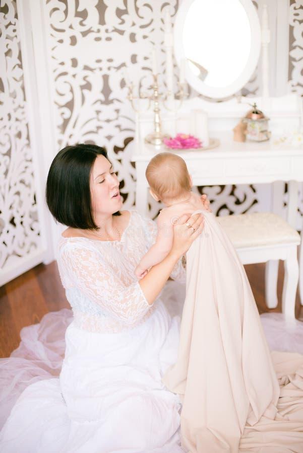Jong mamma met een baby in haar wapens in de heldere slaapkamer royalty-vrije stock foto's