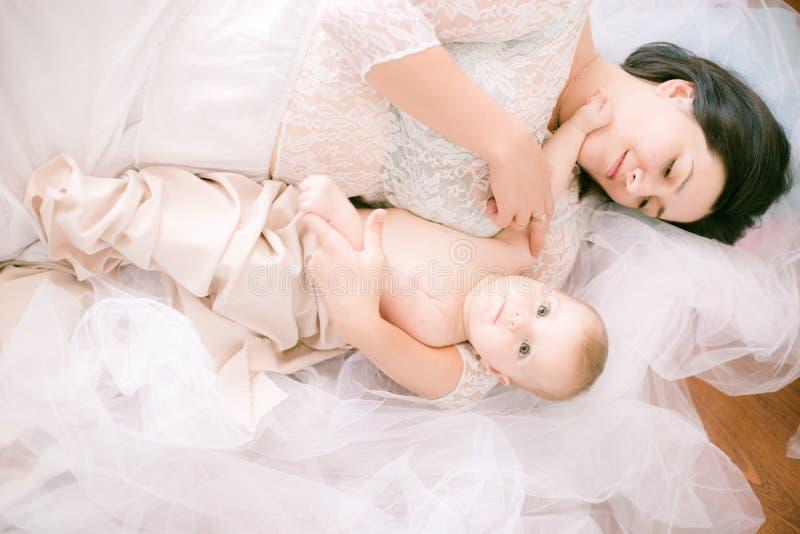 Jong mamma met een baby in haar wapens in de heldere slaapkamer stock afbeelding