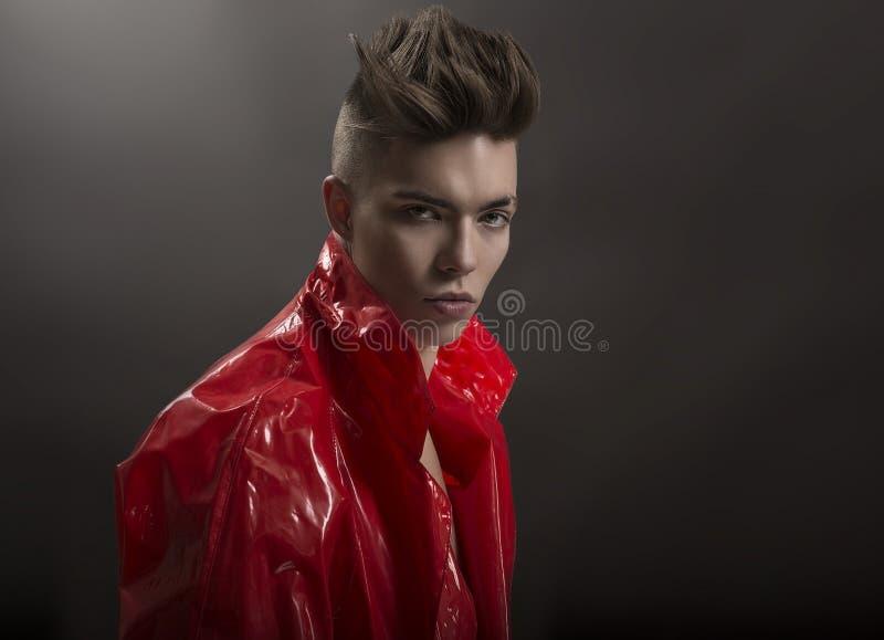 Jong man portret Modieuze knappe Kerel in modieuze rode Lange lakregenjas, Close-up stock foto's