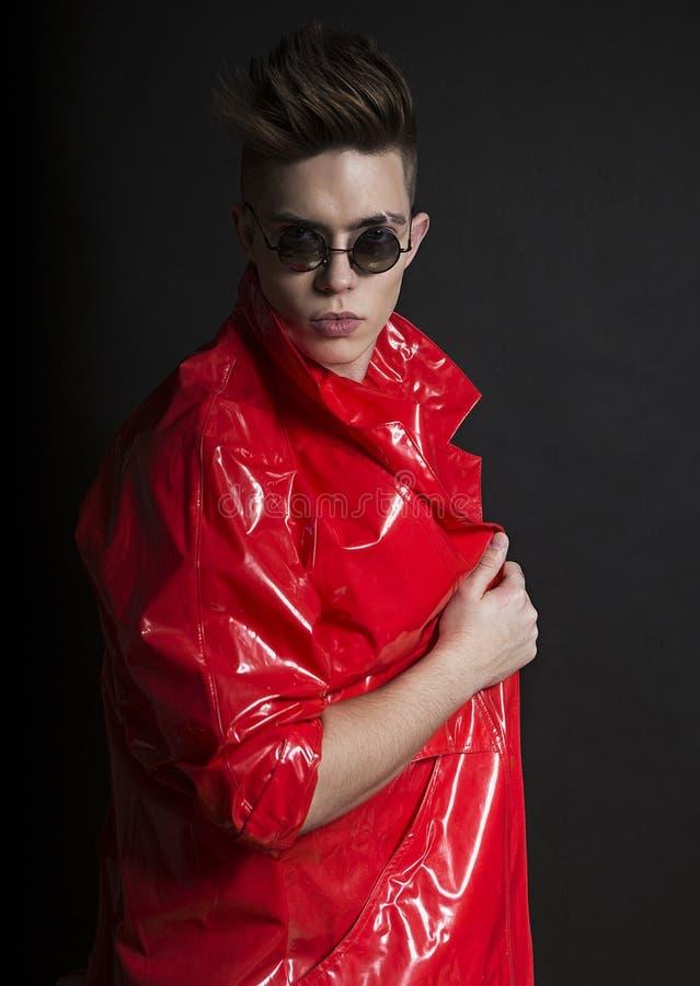 Jong man portret Modieuze knappe sexy Kerel in modieuze rode lakregenjas en ronde zonnebril royalty-vrije stock foto