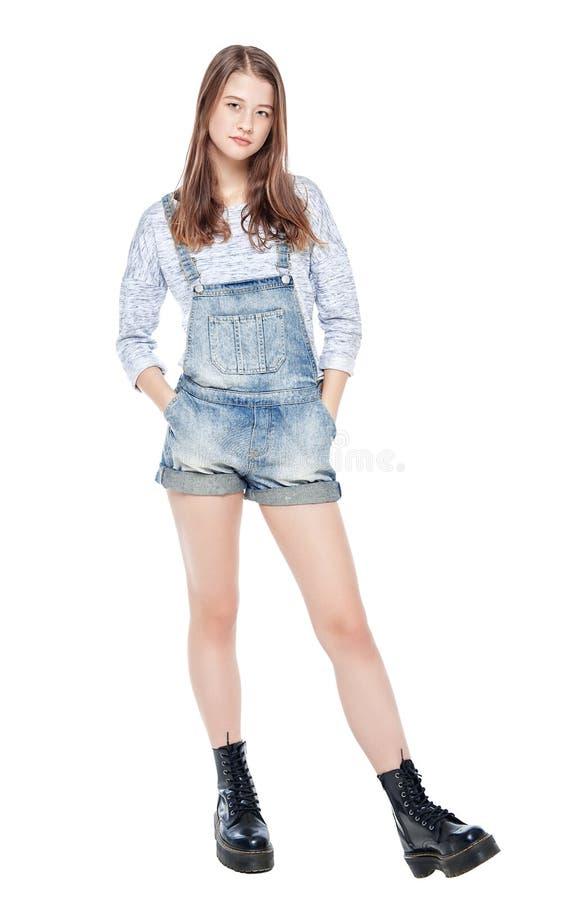 Jong maniermeisje in jeansoverall geïsoleerd stellen stock foto