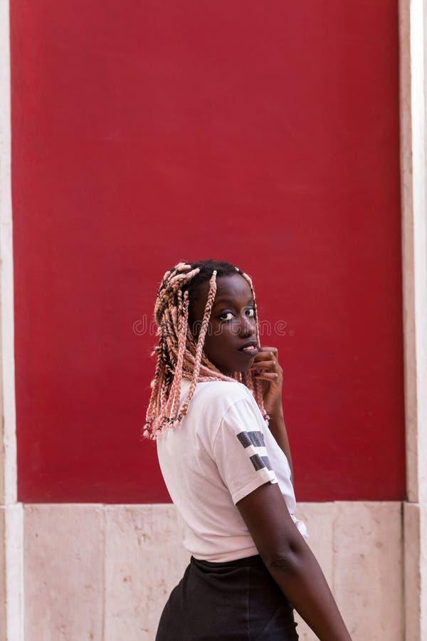 jong maniermeisje op rode muurachtergrond op straat stock foto