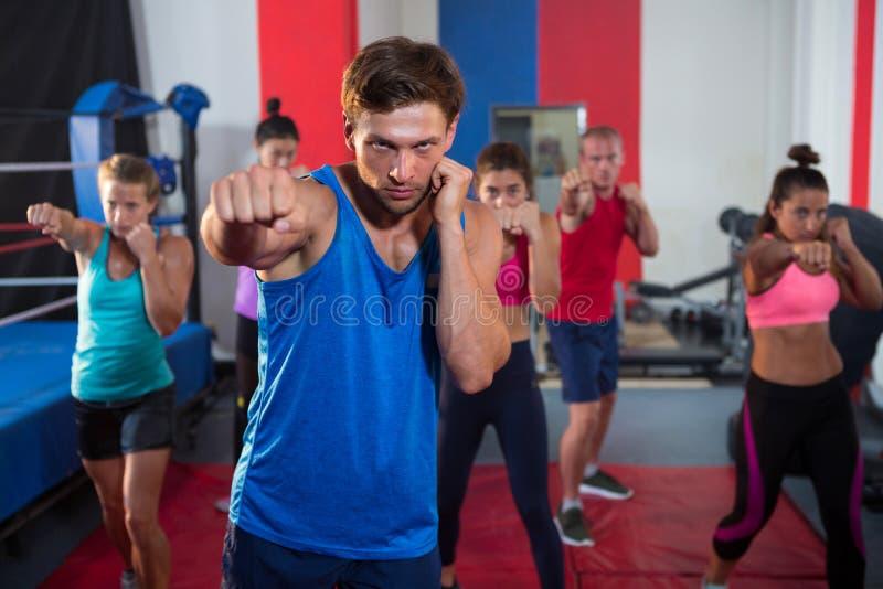 Jong mannelijk en vrouwelijk atletenponsen door boksring stock foto