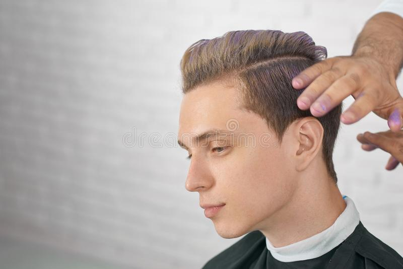 Jong mannelijk model die op nieuw kapsel met lilac haarkleuring wachten royalty-vrije stock afbeeldingen