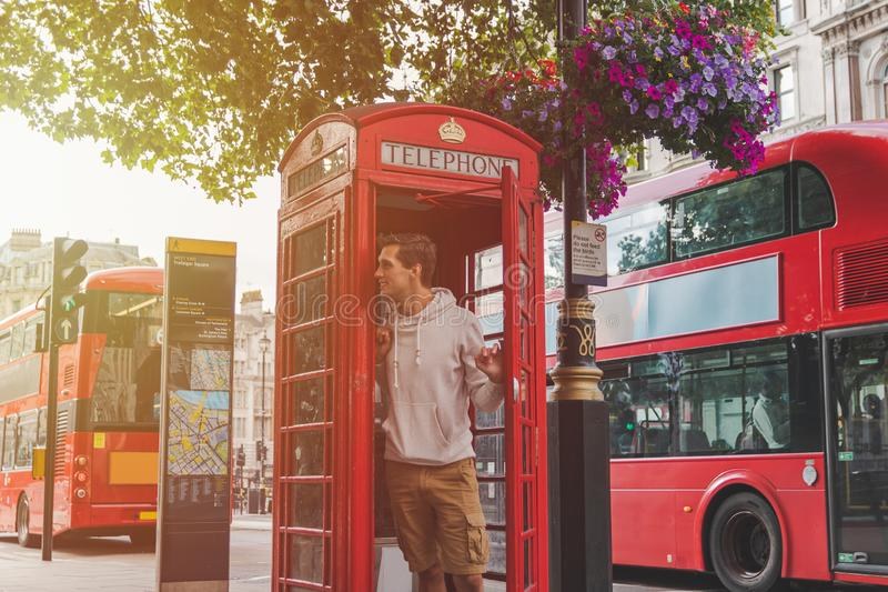 Jong mannetje die in Londen uit van een telefooncel met rode bussen in de rug kijken royalty-vrije stock foto