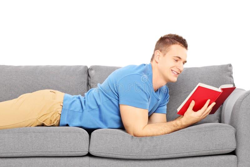Jong mannetje die op een moderne laag liggen en een boek lezen stock fotografie