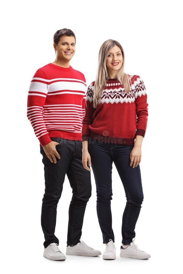 Jong mannetje en wijfje die Kerstmis rode sweaters en het stellen dragen stock afbeelding