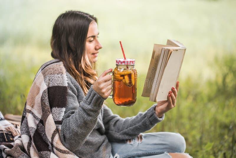 Jong meisje in aard met een drank in hand lezing een boek stock fotografie
