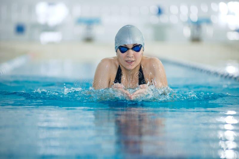 Jong meisje in beschermende brillen die de stijl van de schoolslagslag zwemmen stock foto's