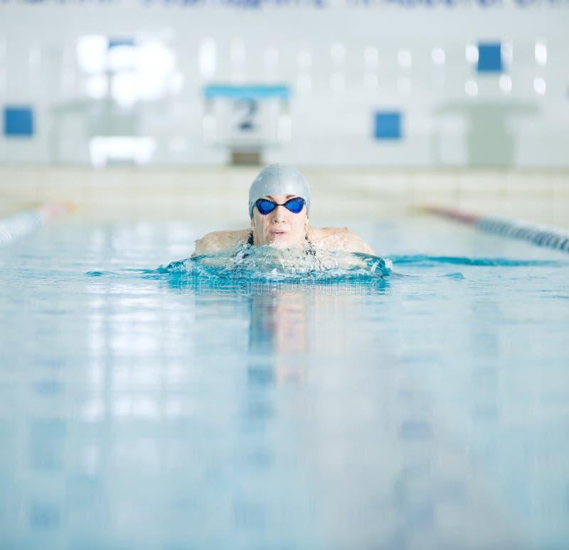 Jong meisje in beschermende brillen die schoolslagslag zwemmen stock fotografie