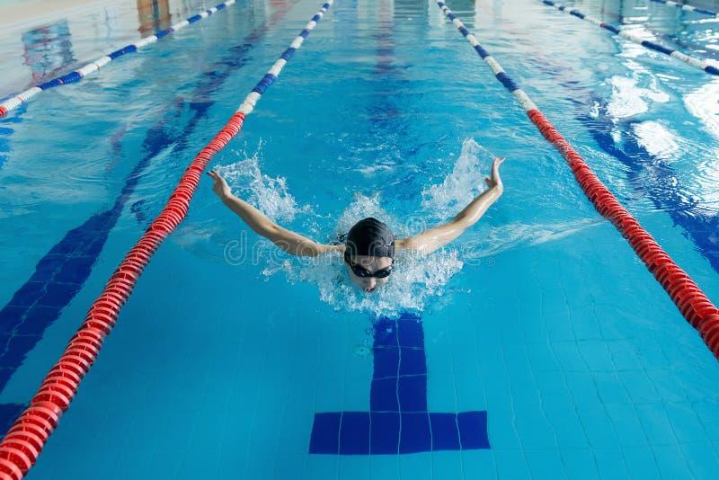 Jong meisje in beschermende brillen en GLB-het zwemmen vlinderslagstijl in de blauwe waterpool royalty-vrije stock fotografie