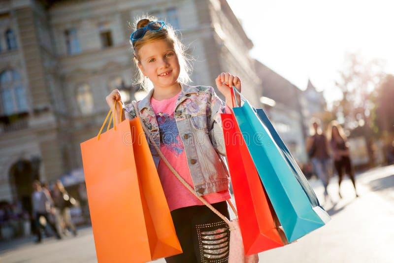 Jong meisje bij de straat met het winkelen zakken royalty-vrije stock afbeeldingen
