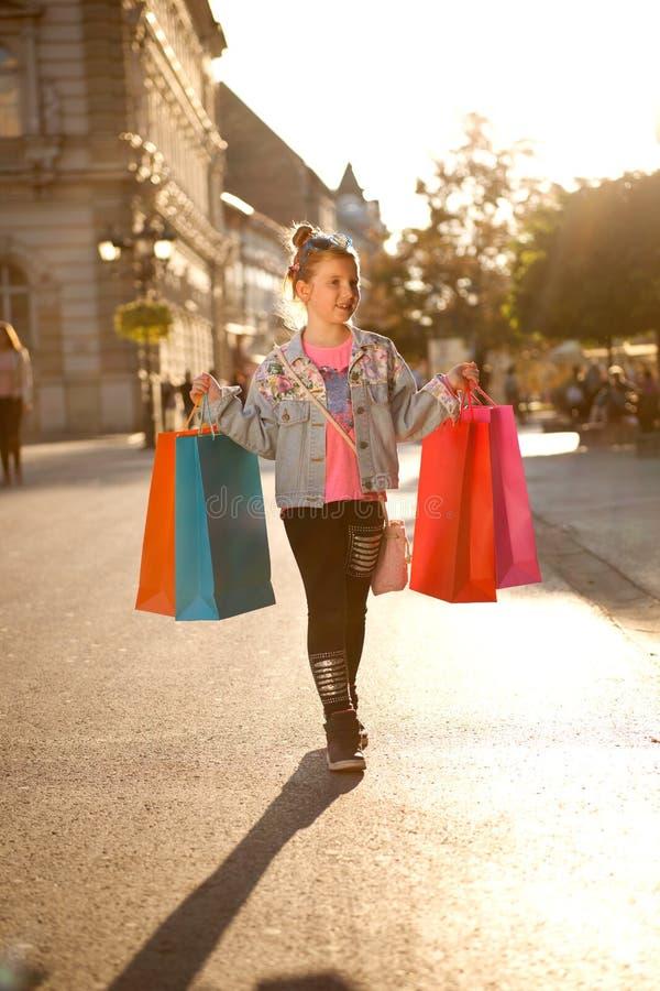 Jong meisje bij de straat met het winkelen zakken royalty-vrije stock foto's