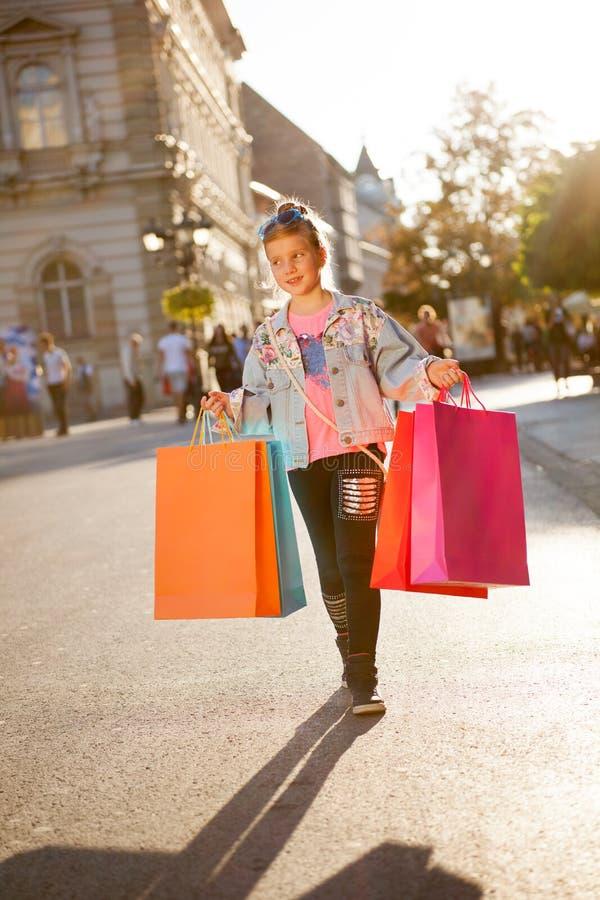 Jong meisje bij de straat met het winkelen zakken stock fotografie