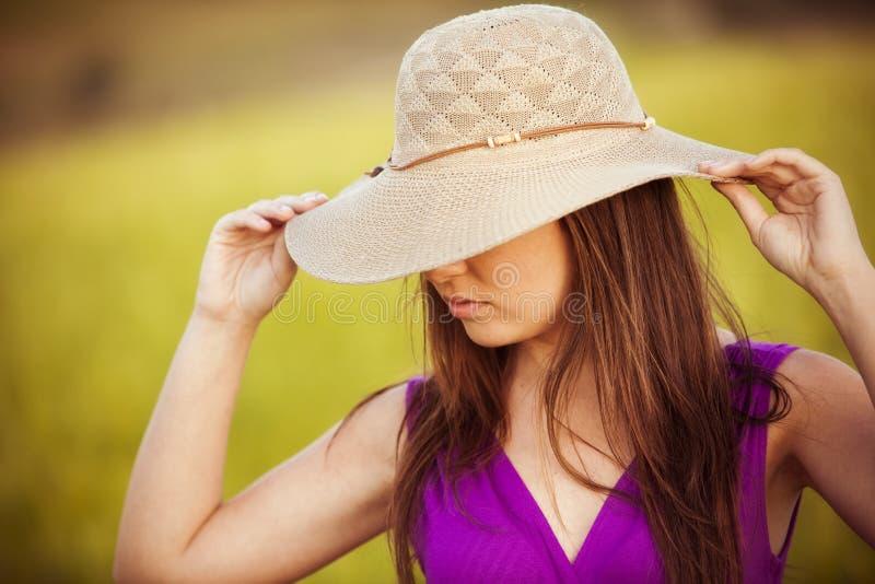 Het verbergen achter haar hoed stock afbeeldingen