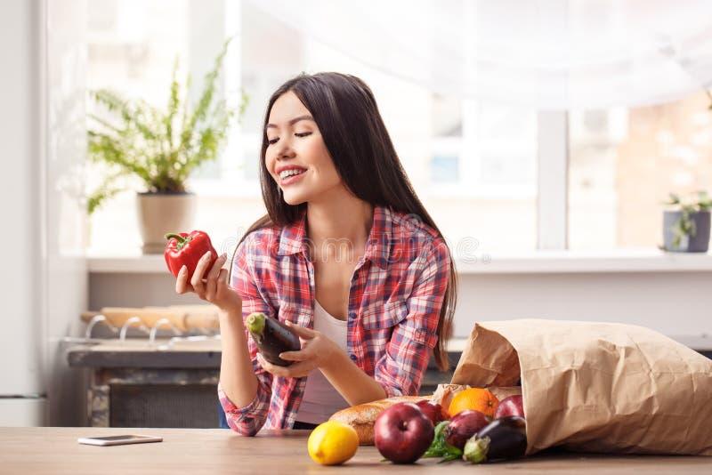 Jong meisje bij keuken gezonde levensstijl status die groene paprika blije dichtbijgelegen zak bekijken op lijst stock fotografie