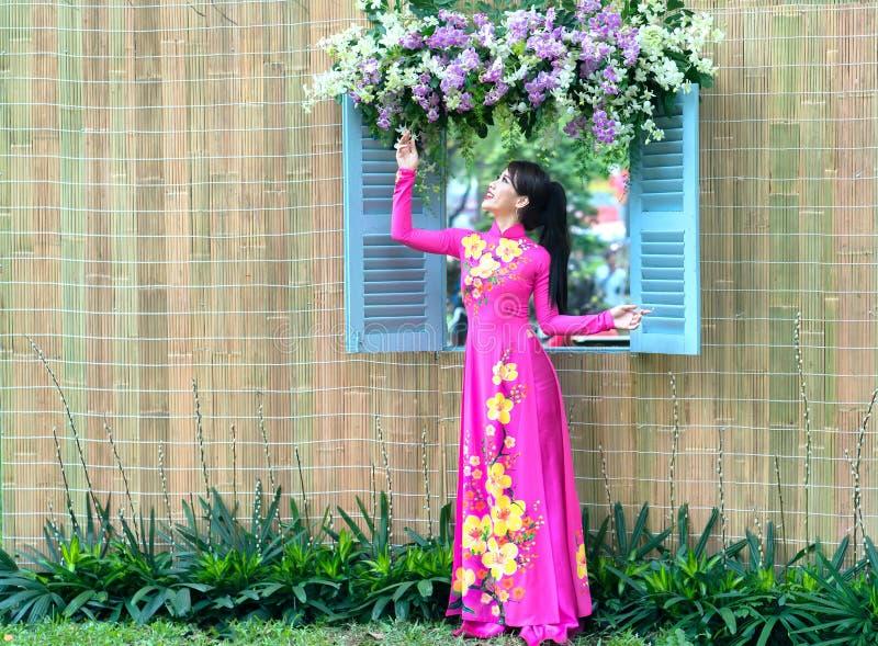 Jong meisje bij venster het letten op bloemen in lang overhemd stock foto
