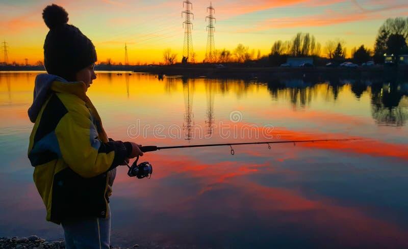Jong meisje bij zonsondergang die een vis vangt royalty-vrije stock foto's