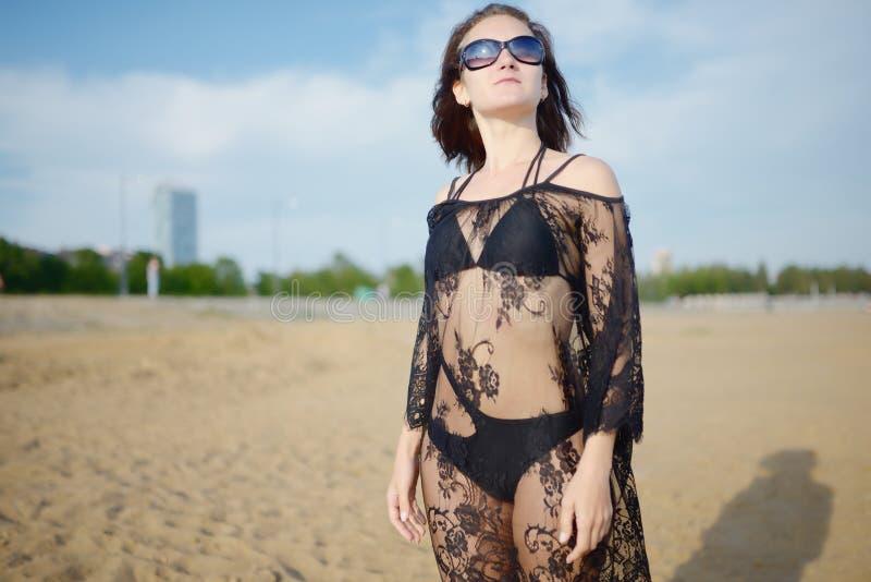 Jong meisje in bikini en transparante zwarte kleding royalty-vrije stock afbeelding