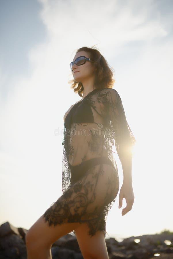 Jong meisje in bikini en transparante zwarte kleding royalty-vrije stock afbeeldingen