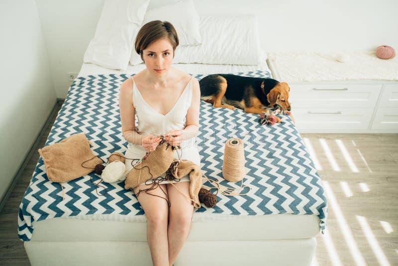 Jong meisje craftwoman in nachtjapon die camera bekijken terwijl het breien van sweater op bed Leuke straathondhond bovendien Fre stock foto