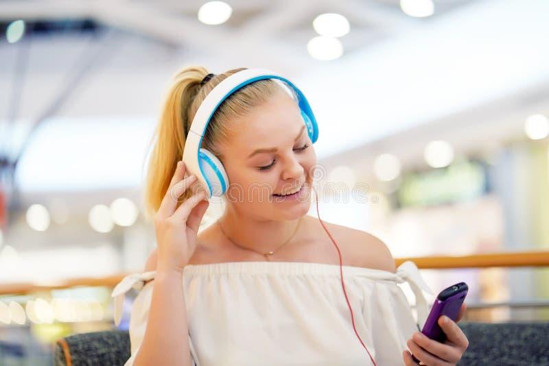 Jong meisje dat aan muziek op hoofdtelefoons luistert stock foto's