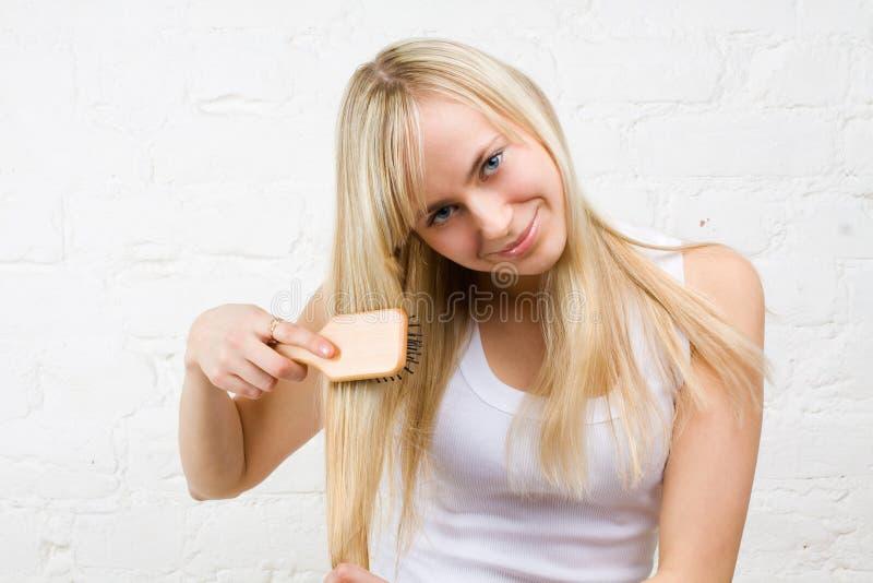 Jong meisje dat blonde haar kamt stock foto