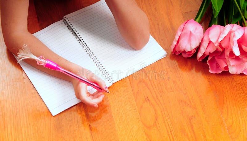 Jong meisje dat in dagboek schrijft royalty-vrije stock afbeelding