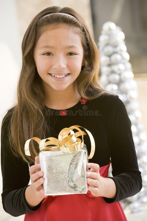 Jong Meisje dat, de Gift van Kerstmis van de Holding glimlacht stock afbeelding