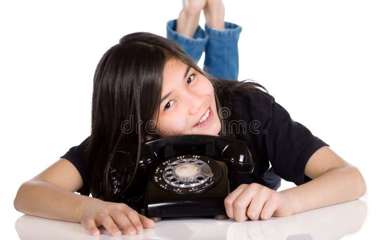 Jong meisje dat door oude telefoon ligt royalty-vrije stock afbeelding