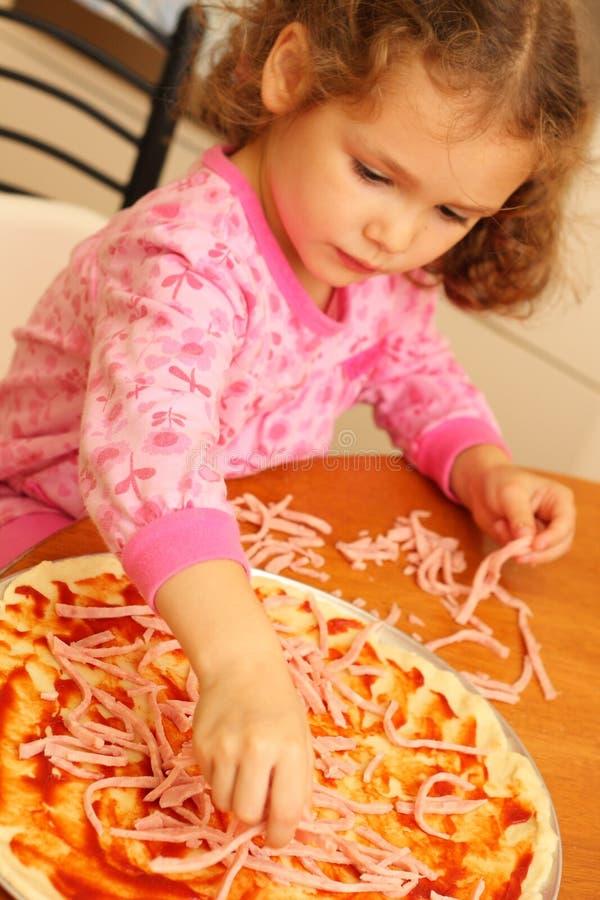 Jong meisje dat eigengemaakte pizza voorbereidt royalty-vrije stock afbeeldingen