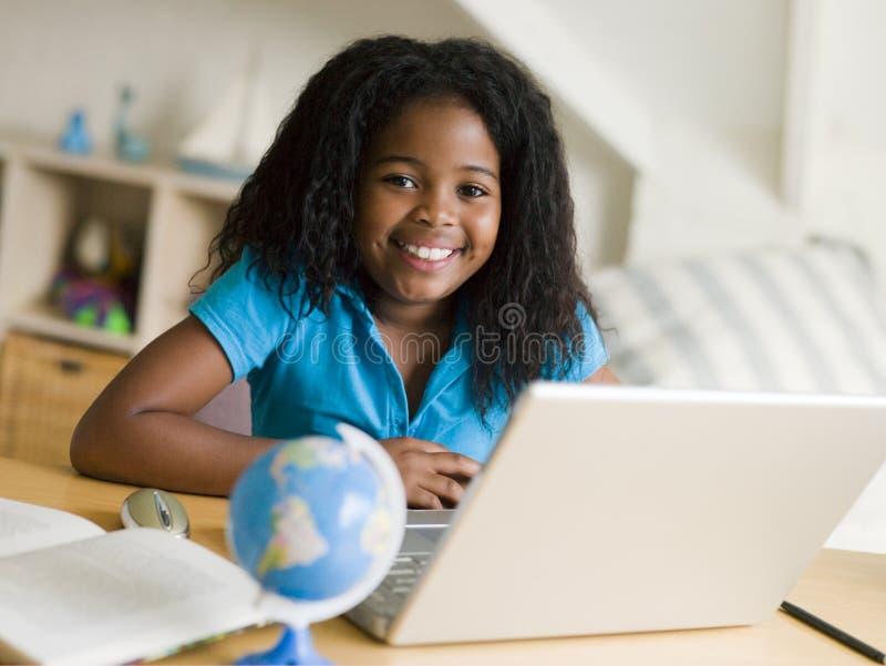 Jong Meisje dat Haar Thuiswerk op Laptop doet stock foto's