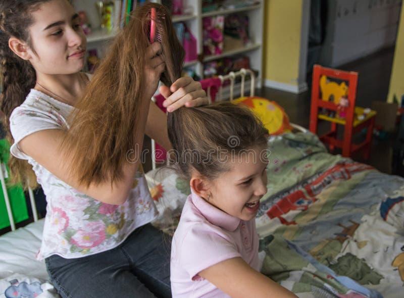 Jong meisje dat haar vriendenhaar vlecht Glimlachend meisje tijdens vlechtenhaar stock afbeelding