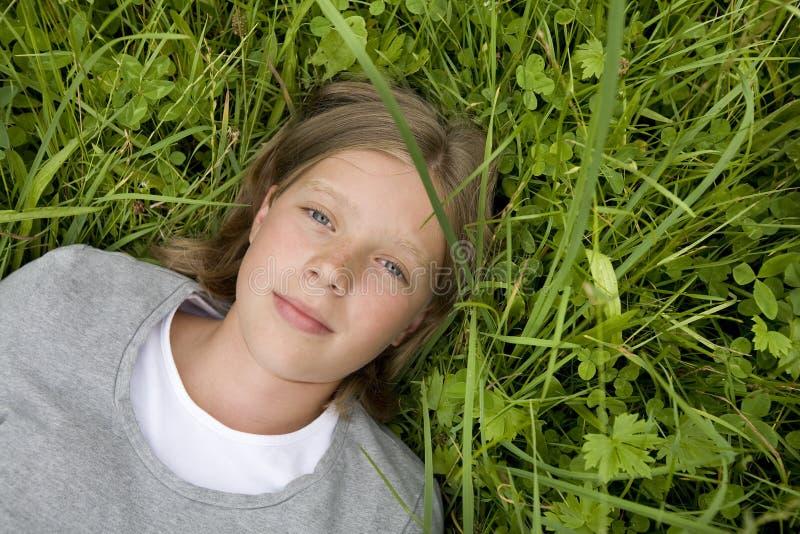 Jong meisje dat in het gras ligt dat droomt van? royalty-vrije stock foto