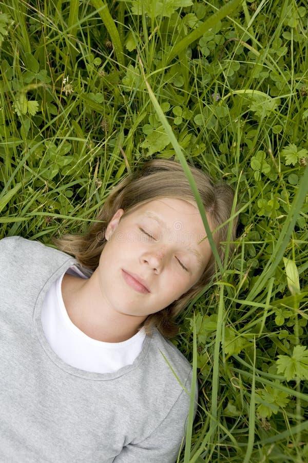Jong meisje dat in het gras ligt dat droomt van? stock foto's