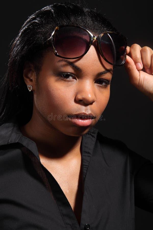 Jong meisje dat met houding zonnebril draagt stock foto's