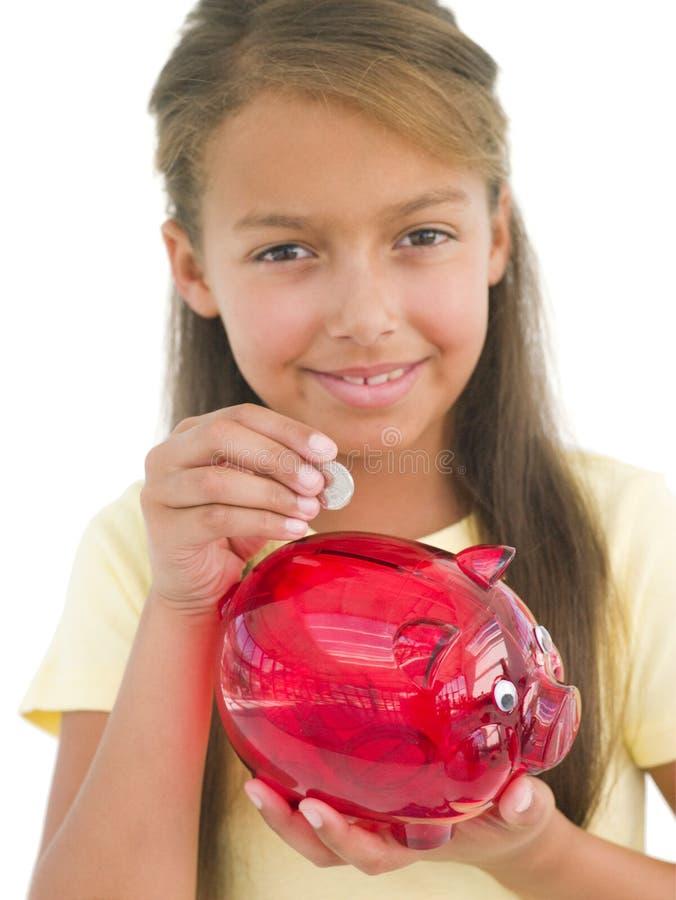 Jong meisje dat muntstuk zet in spaarvarken stock afbeeldingen