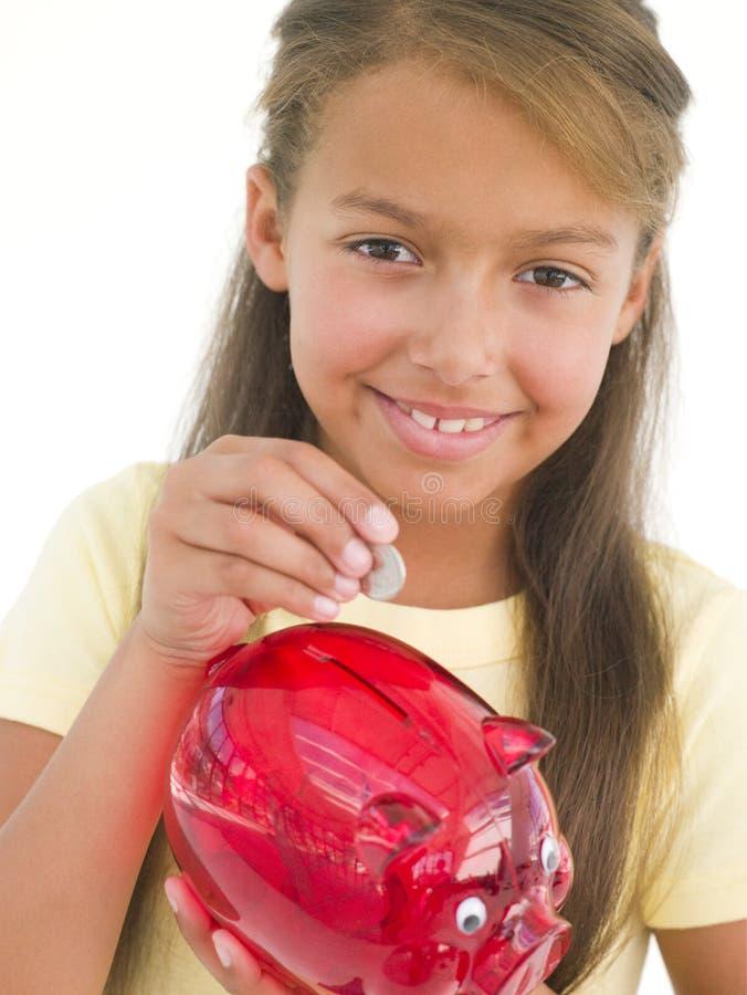 Jong meisje dat muntstuk zet in spaarvarken stock foto
