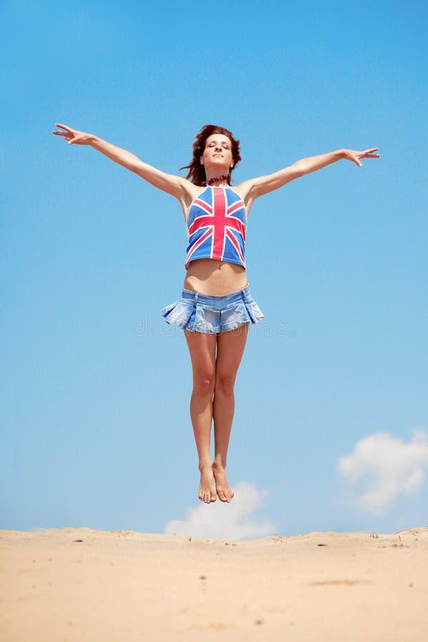 Jong meisje dat op een achtergrond van blauwe hemel springt royalty-vrije stock afbeeldingen