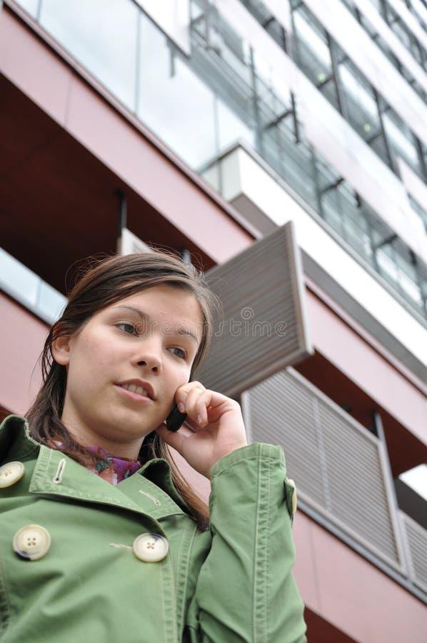 Jong meisje dat op mobiele telefoon spreekt royalty-vrije stock afbeelding