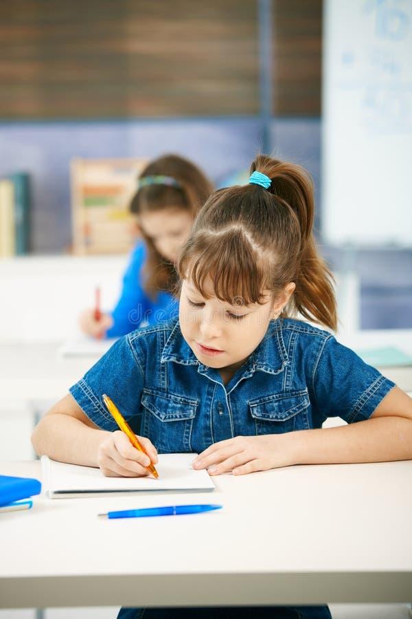Jong meisje dat op school schrijft royalty-vrije stock fotografie