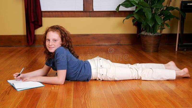 Jong meisje dat op vloer het schrijven legt royalty-vrije stock afbeelding