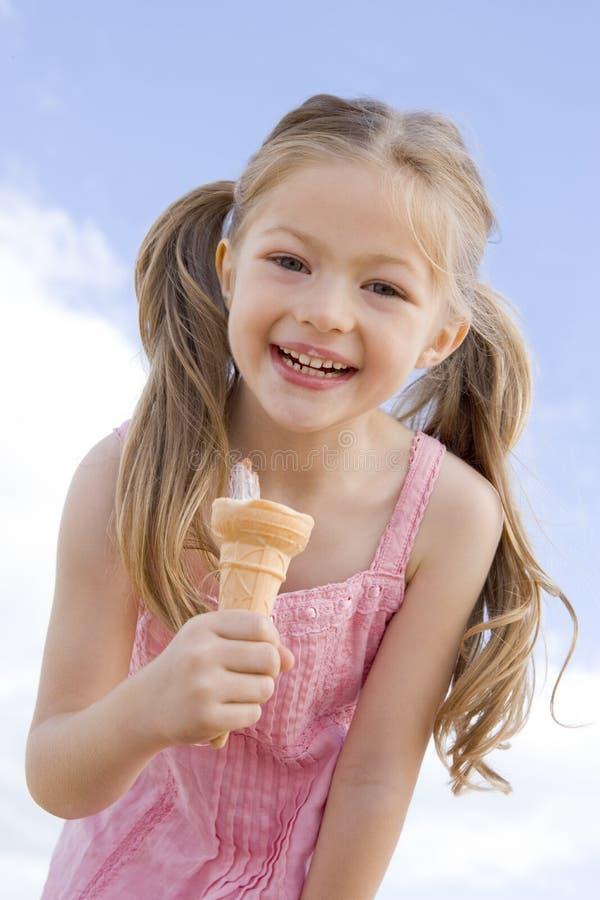 Jong meisje dat in openlucht roomijskegel eet stock foto