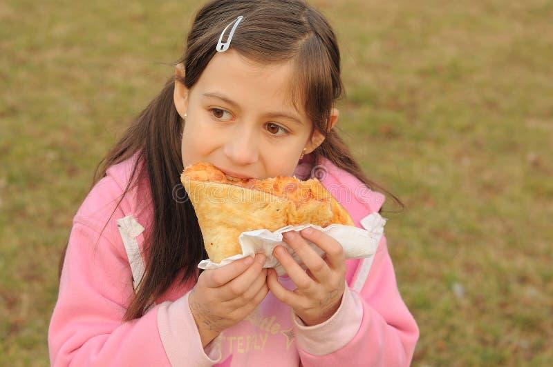 Jong meisje dat pizza eet royalty-vrije stock foto's