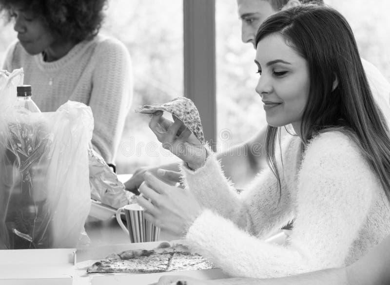 Jong meisje dat pizza eet stock afbeelding