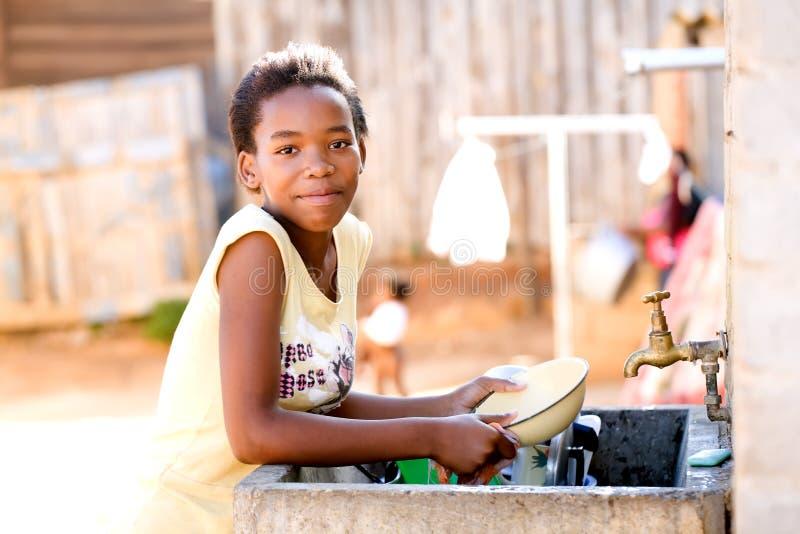 Jong meisje dat schotels doet royalty-vrije stock afbeeldingen